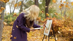 Blonde girl artist draws among falling leaves in the autumn park. Young beautiful girl artist with blonde hair in purple coat drawing a picture on the easle royalty free stock image