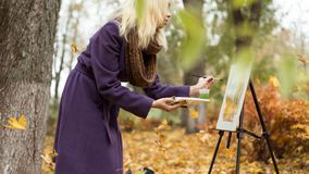 Blonde girl artist draws among falling leaves in the autumn park royalty free stock image