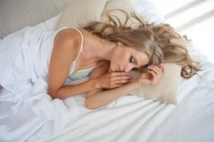 Blonde girl asleep in the bedroom dreams holiday morning Stock Photography