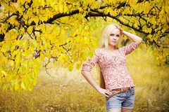 Blonde girl in the autumn park. Beautiful long-haired blonde girl in the autumn park. trendy casual clothing (shirt and jeans shorts with leather belt). outdoor Royalty Free Stock Images