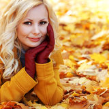 Blonde girl in Autumn Park with Maple leaves. Fashion. Beautiful Woman with leather gloves. Fall Royalty Free Stock Photography