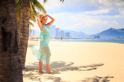 blonde girl in azure with hands above head near palms on beach Royalty Free Stock Photos
