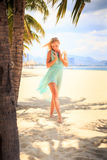 blonde girl in azure with hands on breast near palms on beach Stock Images