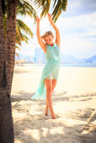 blonde girl in azure with hands on breast near palms on beach Stock Photos