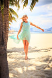 blonde girl in azure with hands on breast near palms on beach Royalty Free Stock Photos
