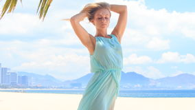Blonde girl in azure lifts hair up under wind on beach stock video footage