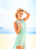 blonde girl in azure looks into camera on beach Stock Images