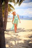 Blonde girl in azure looks into camera on beach Royalty Free Stock Images