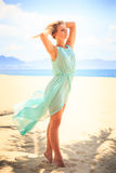 Blonde girl in azure looks into camera on beach Stock Photography