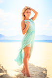 Blonde girl in azure looks into distance on beach Royalty Free Stock Images