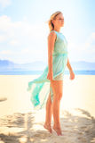 Blonde girl in azure looks into distance on beach Stock Images