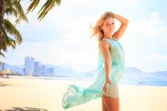 Blonde girl in azure looks forward wind shakes hair on beach Stock Image