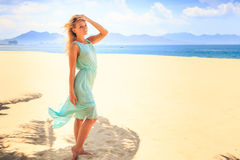 blonde girl in azure looks forward wind shakes hair on beach Royalty Free Stock Image