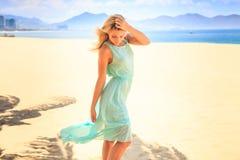 blonde girl in azure looks forward wind shakes hair on beach Stock Photos