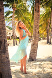 Blonde girl in azure on tiptoe with hand on head among palms Royalty Free Stock Images