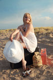 Blonde girl with baggage on the beach Royalty Free Stock Images