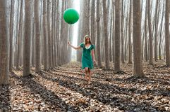Blonde girl with balloon in a poplar forest Royalty Free Stock Photos