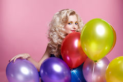 Blonde girl with balloons. Portrait of beautiful blonde girl with balloons celebrating birthday royalty free stock photos