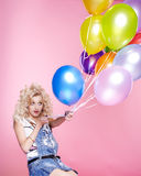 Blonde girl with balloons. Portrait of beautiful party blonde girl pulling balloons celebrating birthday royalty free stock photos