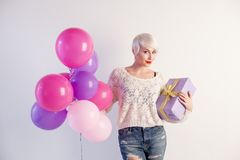 Blonde girl with balloons and gift on a holiday. 1 Stock Photography