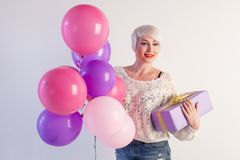 Blonde girl with balloons and gift on a holiday. 1 Stock Photo