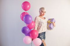 Blonde girl with balloons and gifts for holiday. 1 Stock Photos