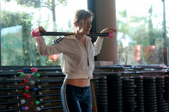 Blonde girl with barbell on her shoulders Stock Photos