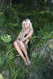 Blonde girl in bathing suit sitting in the forest Royalty Free Stock Photos
