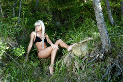 Blonde girl in bathing suit sitting in the forest Stock Image