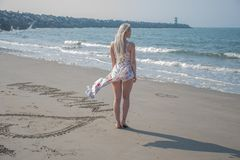 blonde girl in beach dress and wind stock photography
