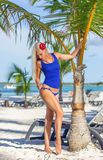 Blonde girl at the beach is posing near palm tree Royalty Free Stock Image