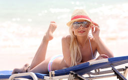 Blonde girl on the beach with summer hat and sunglasses Stock Images