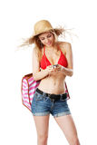 Blonde girl in beachwear switching music on mp3 player. Isolated on white Royalty Free Stock Photography