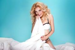 Blonde girl in bed posing. Royalty Free Stock Image