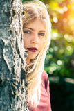 Blonde girl behind a tree. Blonde girl check and looks from behind a tree Stock Photos