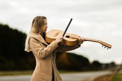 Blonde girl in a beige coat plays the guitar like a violin standing on the edge of autumn motorway. On blurred background royalty free stock images