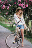 Blonde girl with bicycle near oleanr flowers. Blonde girl wearing hat and shorts with vintage bicycle and pink oleander tree behind her in park. Happy girl on Royalty Free Stock Image