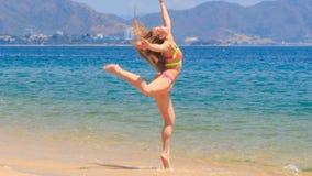 Blonde girl in bikini jumps swings in shallow water on beach. Blonde slim female gymnast in bikini jumps and swings in shallow water on beach against mountains stock video