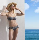 Blonde girl in bikini near the wall with hat Royalty Free Stock Photos