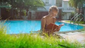 Blonde girl in bikini reads book in pool leaning on barrier stock footage