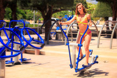 Blonde girl in bikini trains on stepper in park near beach Royalty Free Stock Photo
