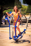 Blonde girl in bikini trains on stepper in park near beach Royalty Free Stock Photography