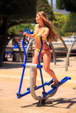 Blonde girl in bikini trains on stepper in park near beach Royalty Free Stock Photo