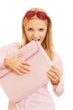 Blonde girl biting folder Royalty Free Stock Images