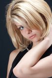 Blonde girl in black. Against black background stock photo