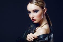 Blonde girl on black background close-up. Stock Image