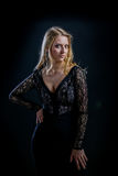 Blonde girl on a black background in  dark guipure dress Royalty Free Stock Images