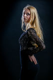 Blonde girl on a black background in  dark guipure dress Royalty Free Stock Image