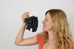 Blonde sensual girl with black bunch of grapes Stock Photo