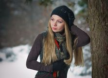 blonde girl with black cap play in winter snow Royalty Free Stock Photo